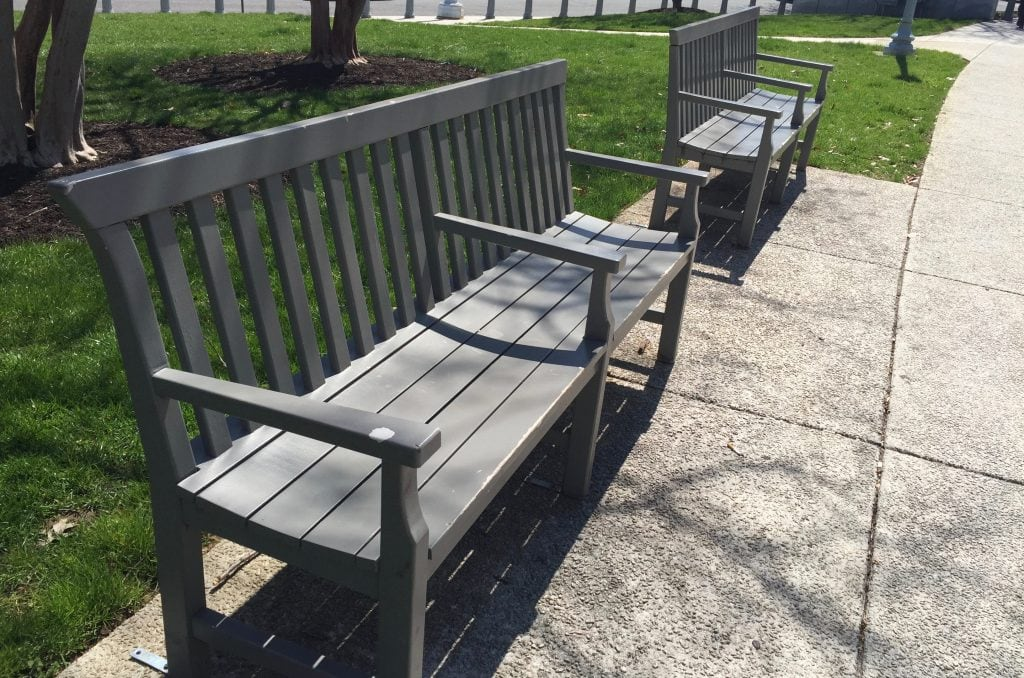 A photograph of two gray wood benches that each have a third armrest in the middle.