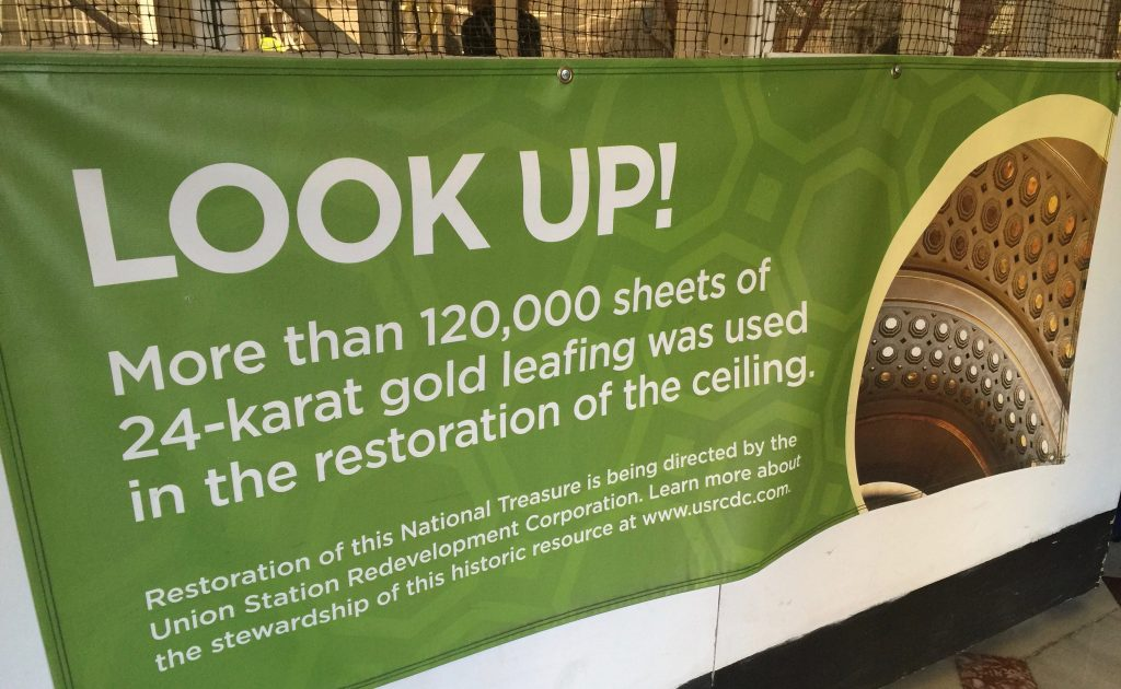 """A Photograph of a banner sign that reads """"Look Up! More than 120,000 sheets of 24-karat gold leafing was used in the restoration of the ceiling."""""""