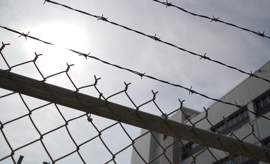 barbed wire and chain link fence with prison in background