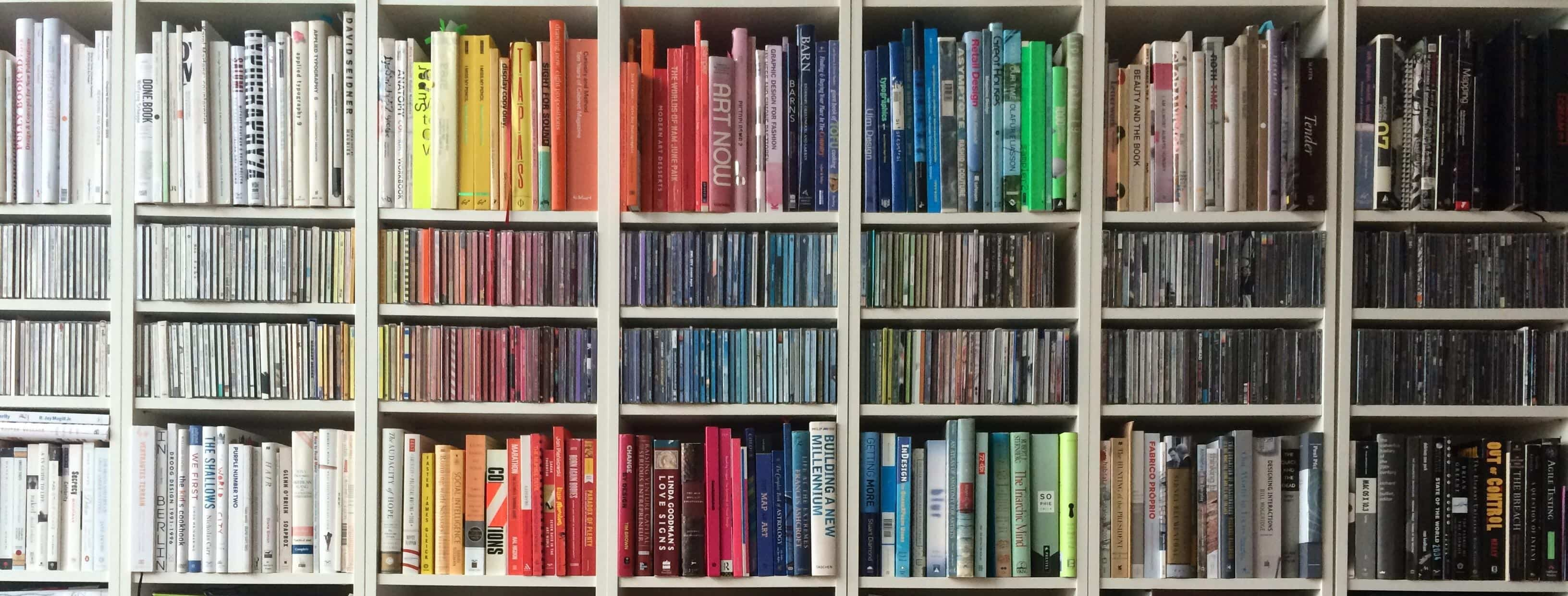 Alt Text: A photograph of a bookshelf with the spines arranged by color from white to yellow to red to blue to green to gray to black. Image via Morguefile, http://mrg.bz/tnqPfm