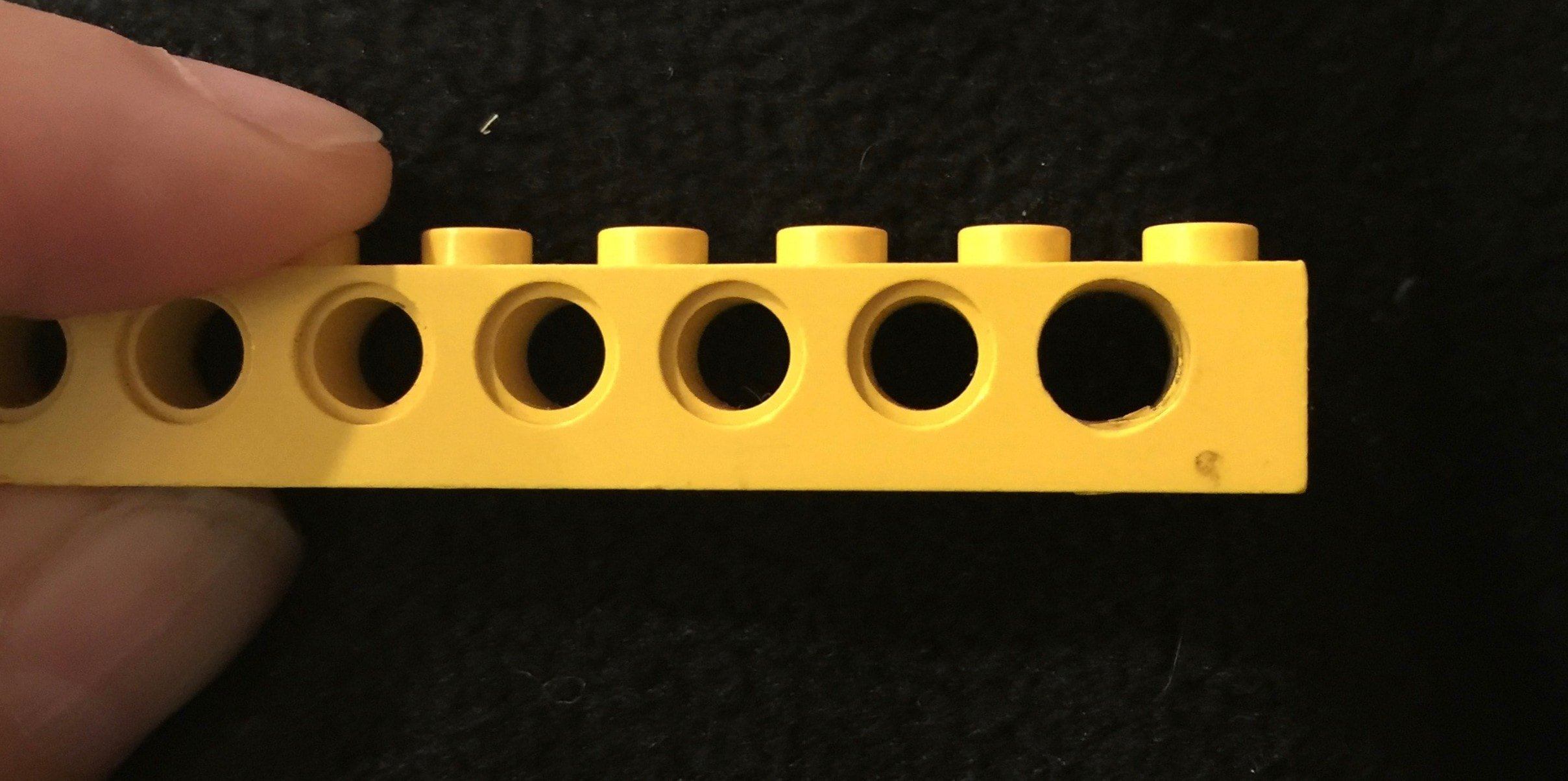 Alt Text: A photograph of a one-by-eight yellow lego piece held by a thumb and forefinger. The background is black. The piece has a series of holes in the side. The final hole has been drilled out to make it slightly larger than the others.
