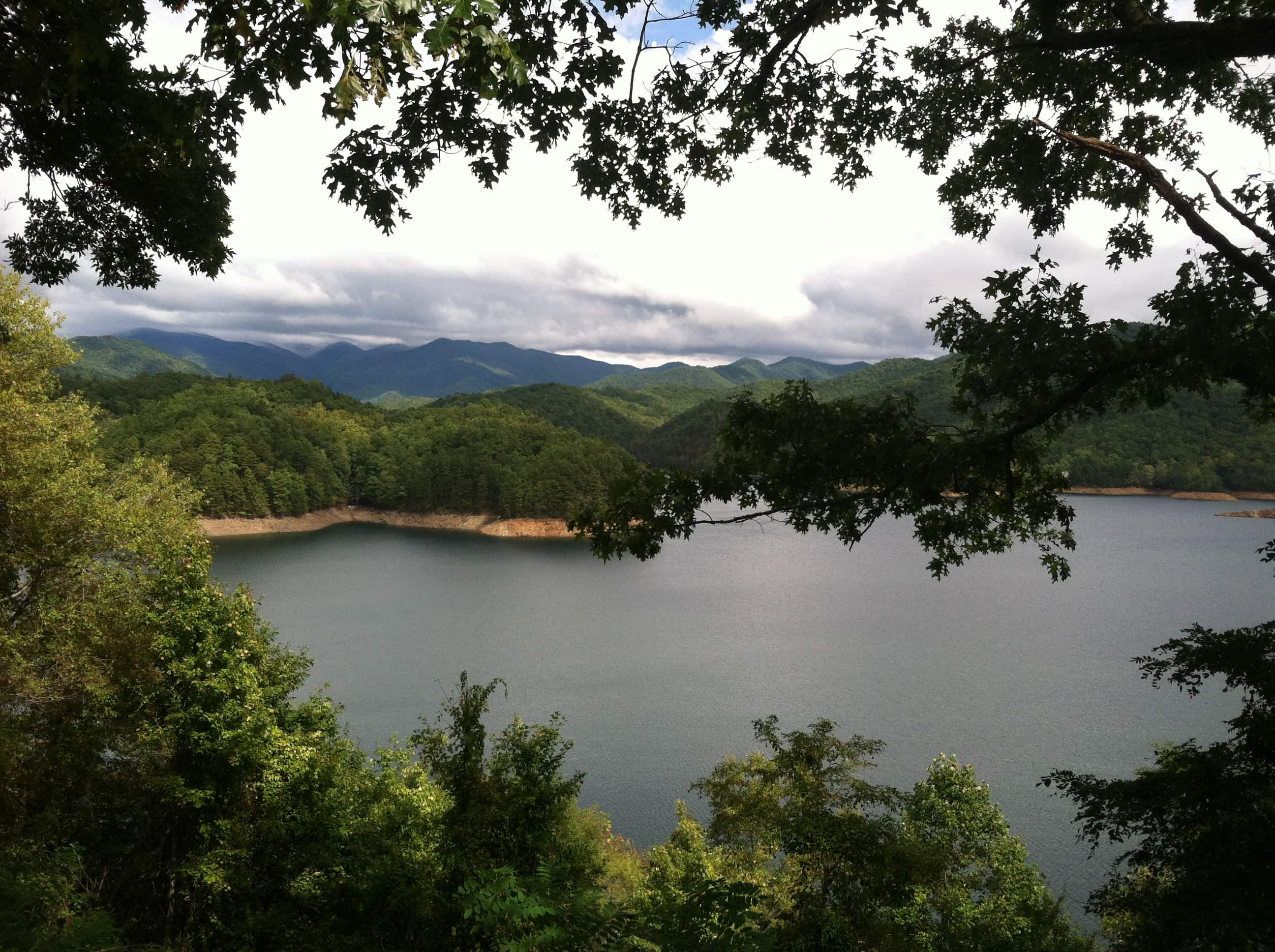 Photograph of Fontana Lake, a reservoir in the Great Smoky Mountains National Park, seen from above, framed by tree branches. In the distance, past the lake, are lush, green mountains.