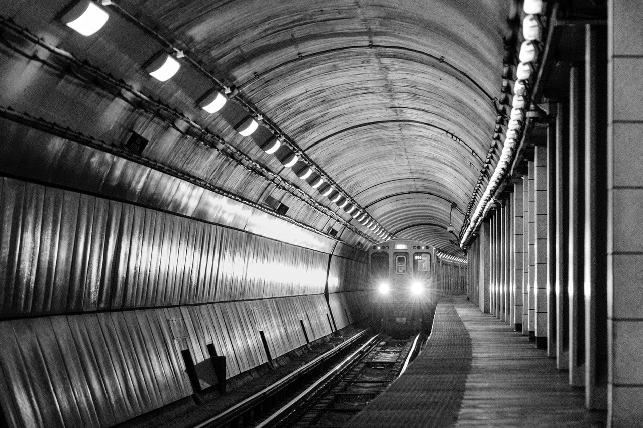 Alt Text: Black and white photograph of a subway train approaching.