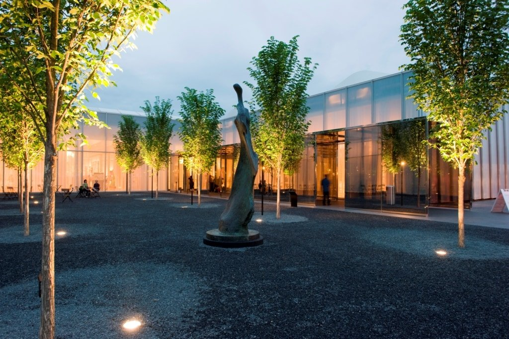 A photograph of the exterior of the North Carolina Museum of Art, a glass and steel structure with a tall, humanoid sculpture in the courtyard, surrounded by trees