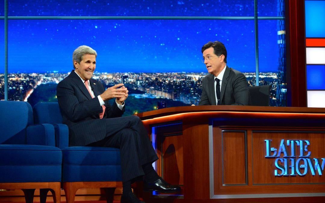 Image Alt Text: A photograph of Stephen Colbert of the set of The Late Show, conversing with guest John Kerry.