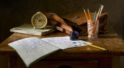 Image via Pixabay. Photograph of a desk with school supplies including a notebook, a jar with pencils, a clock, and a satchel.