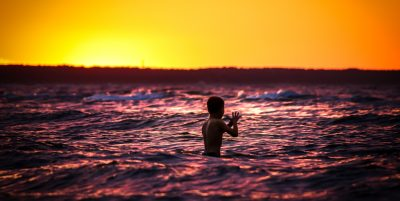 A boy swimming in the ocean at sunset
