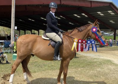 A full-body picture of me on Leroy, ribbons hanging from his bridle.